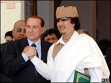 Italian Prime Minister Silvio Berlusconi (left) shakes hands with Libya's Col Muammar Gaddafi  in Benghazi on 30 August