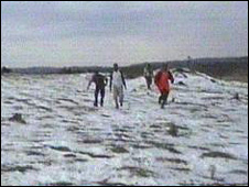Villagers walking across white fields
