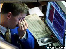 A trader rubs his face as he works on the floor of the New York Stock Exchange, 29 September 2008