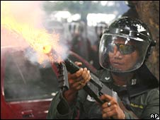 Thai police officer fires teargas shell at anti-government protester on 7 October