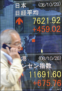 Hombre pasa frente a una pizarra electrónica con el índice Nikkei