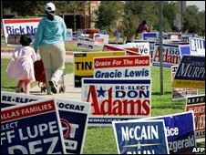 Pedestrians walk along a pavement that is lined with dozens of election signs