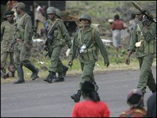 Congolese government soldiers pass displaced people as they return from the front near Goma on Tuesday 11 November 2008