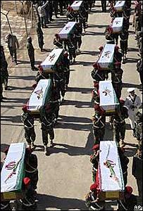 Soldados iranies portando féretros de sus correligionarios caidos en la guerra contra Irak