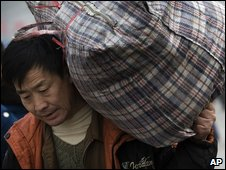 A migrant worker carries his bag as he leaves the Beijing Railway Station, Tuesday, 16 Dec, 2008