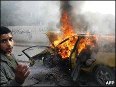A Palestinian boy near a burning car hit by Israeli air strike in the southern Gaza Strip near the Rafah border crossing with Egypt, 11 January 2009