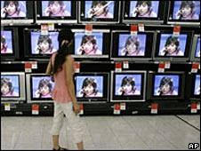 Woman looks at TV screens on Chinese street