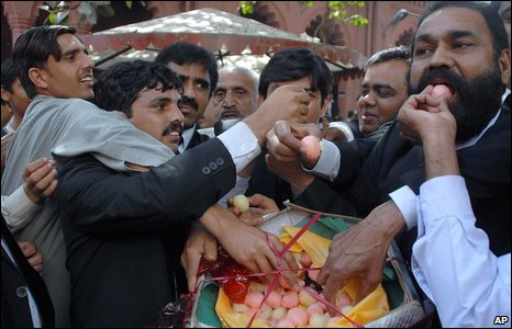 Lawyers grab colourful sweets in the street