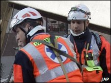 Rescuers remove a body from a university dormitory in L'Aquila