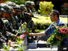 A man hands flowers to soldiers confronting protesters in Bangkok, 13 April