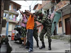 Soldiers frisk young men in a neighbourhood of Medellin after a spate of drug gang-related deaths