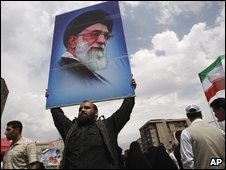 An Iranian man holds a poster of the supreme leader Ayatollah Ali Khamenei at the conclusion of the Friday prayers, in Tehran, Iran on Friday