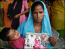 Janaki and baby with pictures of her late husband