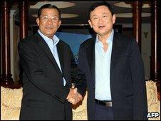 อดีตนายกรัฐมนตรีทักษิณ ชินวัตร (ขวา) จับมือกับนายกรัฐมนตรีฮุน เซนของกัมพูชา (ซ้าย)