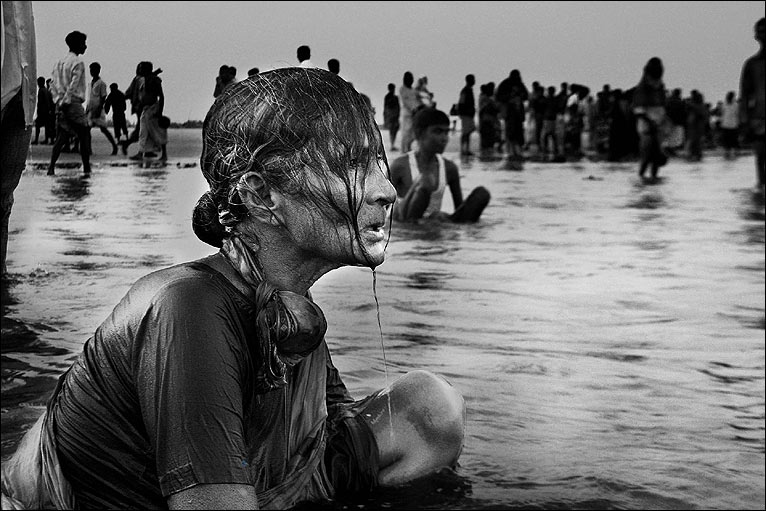 "A woman bathing in the river at the Hindu ""Rash Mela"" festival in the Bay of Bengal."