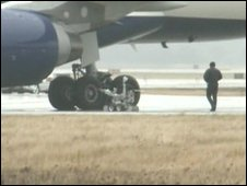 A robot, followed by an official, approaches the airliner as it stands at Detroit airport