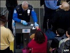 An official checks passengers' documents at Ronald Reagan Washington National Airport in Arlington, Virginia, 29 December 2009