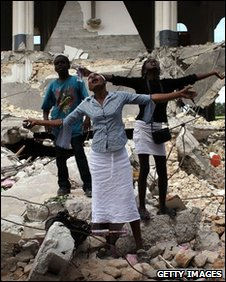 People pray among the ruins of the Sacre Coeur church in Port-au-Prince on 14 January