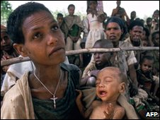 A woman with her baby waits for food and medical care