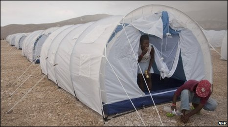 A haitian man washes his feet outside his new tent at the Corail    site