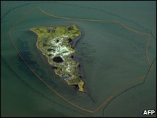 One of the New Harbor Islands is protected by two oil booms  against the oil slick