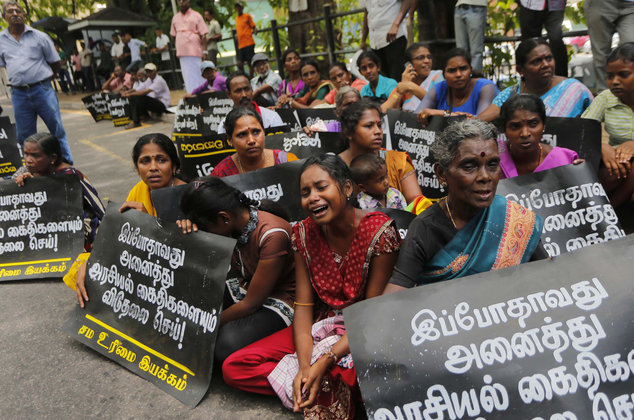 "Family members of ethnic Tamil detainees sit for a silent protest in Colombo, Sri Lanka, Wednesday, Oct. 14, 2015. Relatives and civil rights activists are demanding the Sri Lankan government to release hundreds of minority ethnic Tamils detained without charges for years on suspicion of links to the now-defeated Tamil Tiger rebels. Placards read ""Release all political prisoners now."" (AP Photo/Eranga Jayawardena)"