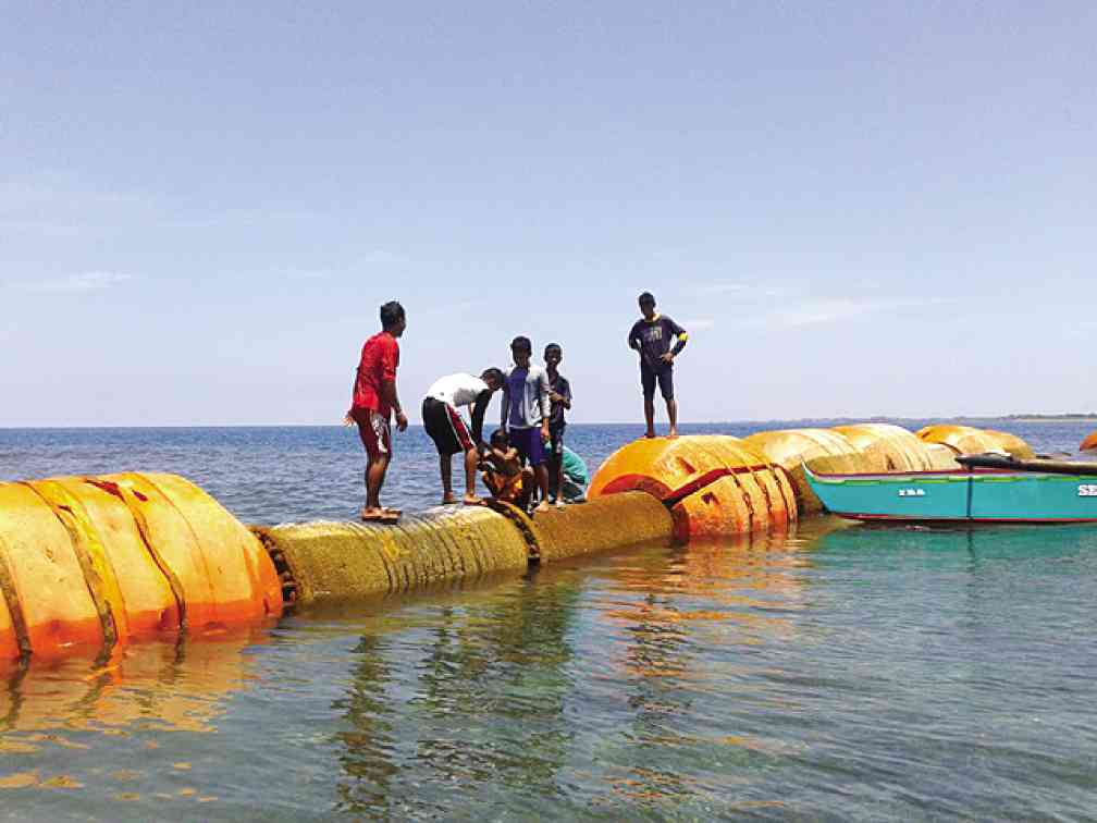 ANOTHER set of a dredge floater assembly with Chinese markings found in the Zambales sea is pulled to the shore of the capital town of Iba on Sunday. The first set of dredge floaters was found by local fishermen off Cabangan, Zambales province, in July. ALLAN MACATUNO/INQUIRER CENTRAL LUZON