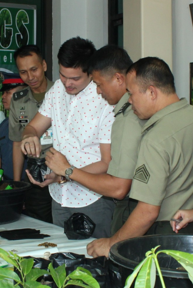 "National Youth Commissioner and actor Dingdong Dantes is assisted in making his own seedling at the soft launch of the ""Race to 1,000,000 Seedlings"" during the Climate Change Summit in Camp General Emilio Aguinaldo on December 7./ AFP PAO"