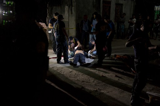 This picture taken on January 18, 2017, shows policemen investigating a body of an alleged drug user on the ground after an unidentified gunmen shot him dead in Manila. AFP PHOTO