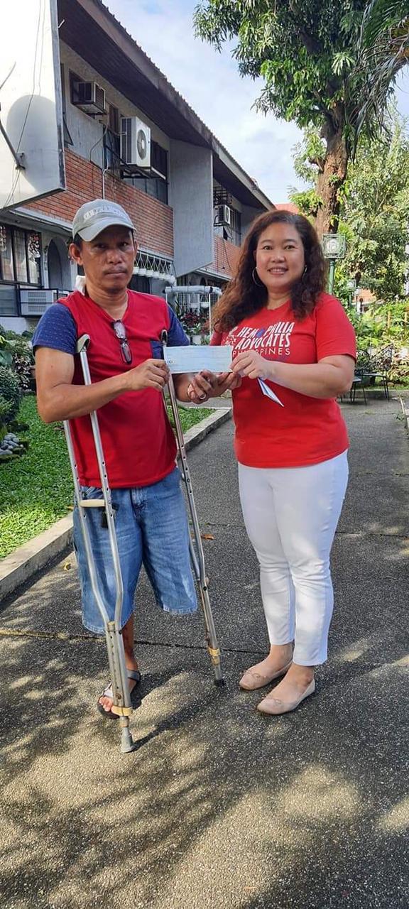 Andrea Trinidad, president of Hemophilia Advocates-Philippines, awards $700 Micro-Enterprise Grant to Rolly Marsula who has Hemophilia A