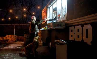 Angelo Re, of North Hills, buys food from the Brisketburgh food truck that is parked in the outside patio of Grist House Craft Brewery. (Antonella Crescimbeni/Post-Gazette)