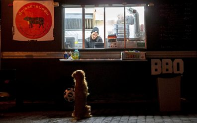 Alex Pusateri, of West View, makes a face at Ginny, Kyle Mientkiewicz's dog, at Grist House Craft Brewery. (Antonella Crescimbeni/Post-Gazette)