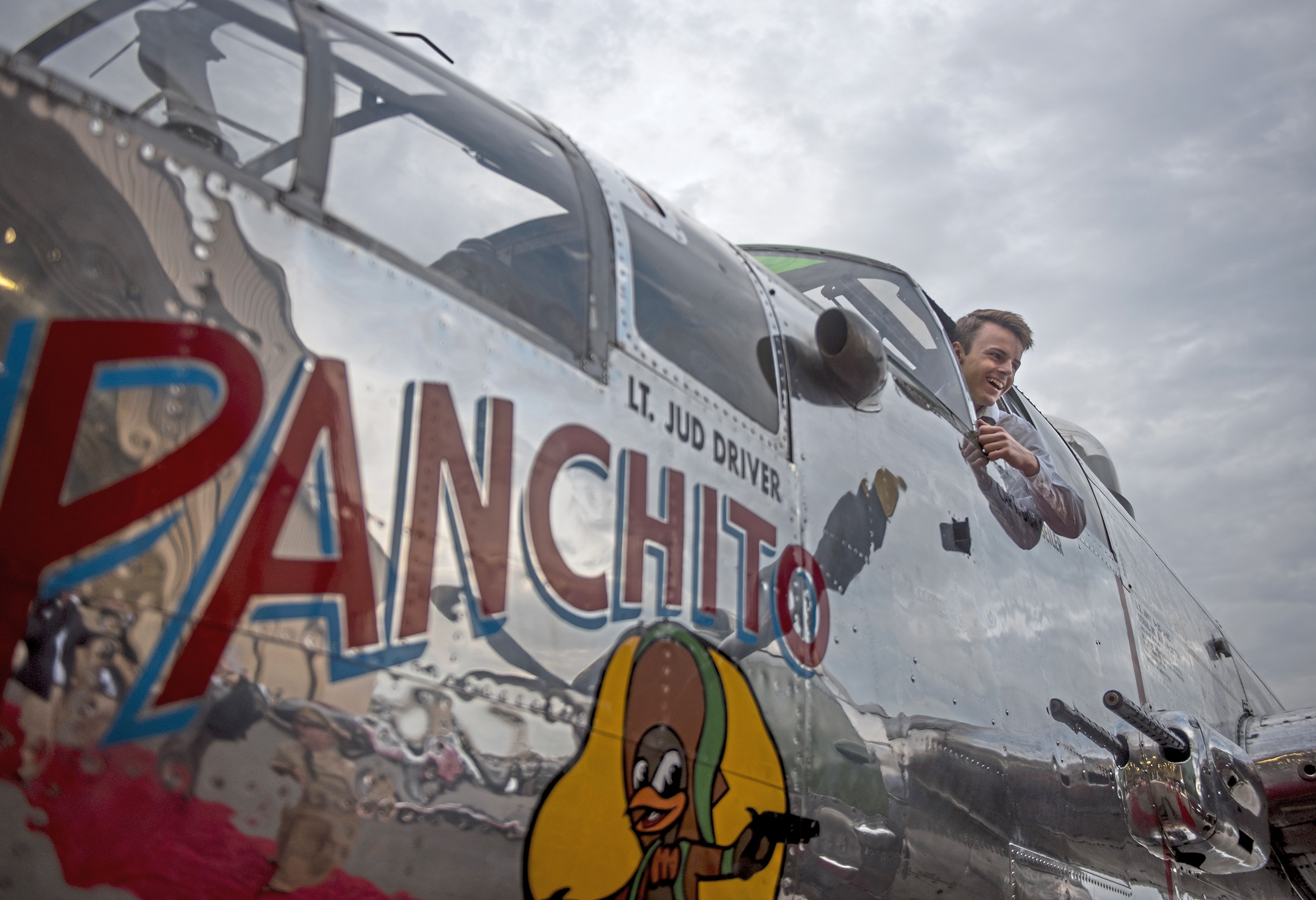 """Luke Lynch hangs out of a B-25 Mitchell """"Panchito"""" at the 2017 Passport to Elegance party, part of the Pittsburgh Vintage Grand Prix. (Haley Nelson/Post-Gazette)"""