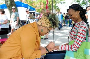 Jamilah Lahijuddin of the North Side works on a henna design for Melissa Thomas of West Mifflin at the 2017 VegFest in Allegheny Commons on the North Side. (Pam Panchak/Post-Gazette)