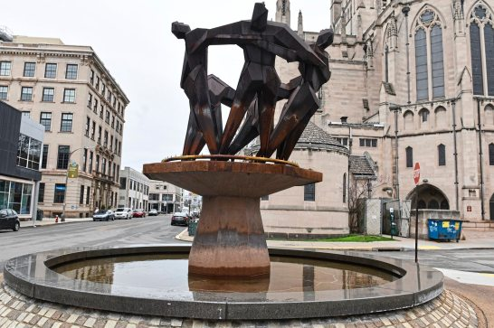 A fountain sculpted by Virgil Cantini depict men holding hands in a circle. The sculpture is at the intersection of Baum Boulevard and South Whitfield Street in East Liberty. (Nate Guidry/Post-Gazette)
