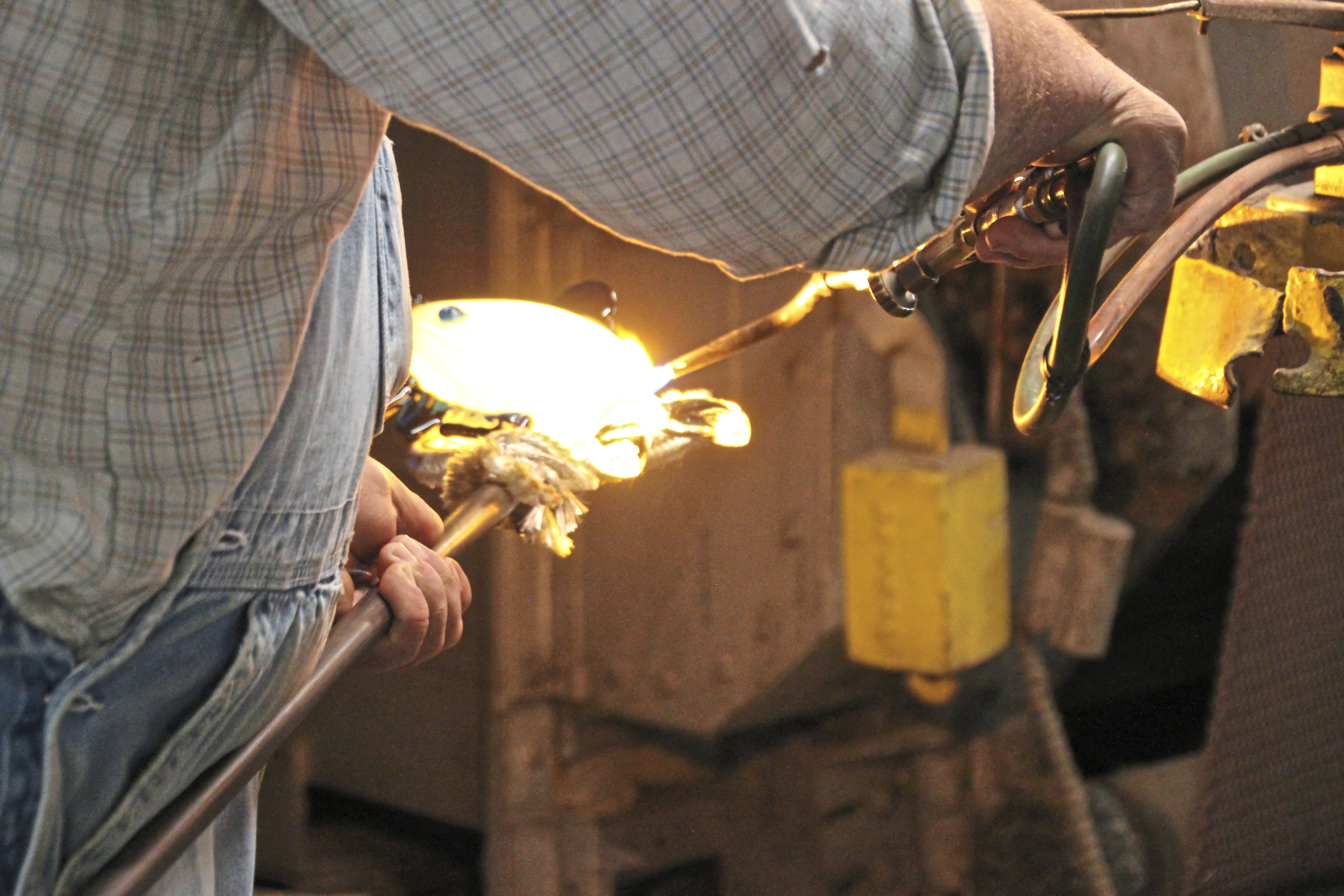 Adding interest to the glass fish being blown and molded at Blenko Glass. (Patricia Sheridan/Post-Gazette)