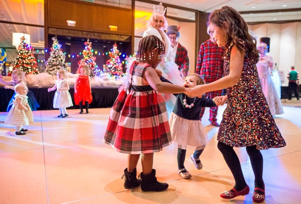 Aurora Prugar, left, Nora Edwards and Charlotte Edwards hold hands and dance together at Pittsburgh Mercy's Reindeer Ball in 2017 at the Westin Convention Center hotel. (Antonella Crescimbeni/Post-Gazette)