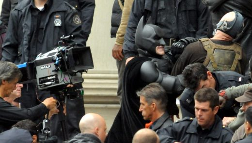 """""""Batman"""" and """"Bane"""" rehearse their """"fighting"""" scene with a walkthrough in front of the Mellon Institute during filming in Oakland. Snow was added in the final takes. (Darrell Sapp / Post-Gazette)"""