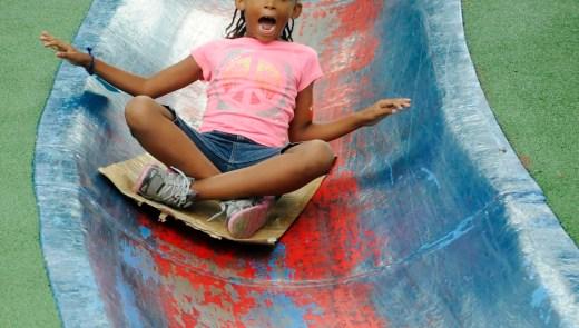 Ailani Mitchell of Homewood, goes down the blue slide at Blue Slide Playground in Frick Park. (Chris Kasprak/Post-Gazette)