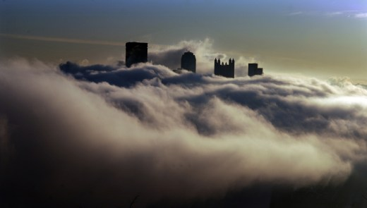 A sea of heavy fog surrounds the Downtown Pittsburgh skyline in this view from the West End Overlook. (Darrell Sapp/Post-Gazette)