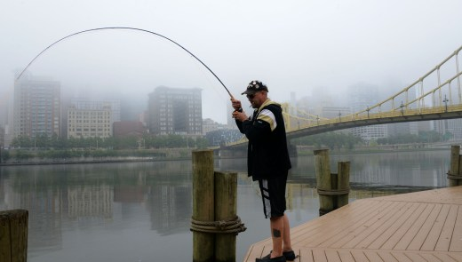 """Russ Stratton , of the North Side, gets a """"bite"""" while fishing in the Allegheny River , on the North Shore. (Darrell Sapp / Post-Gazette)"""