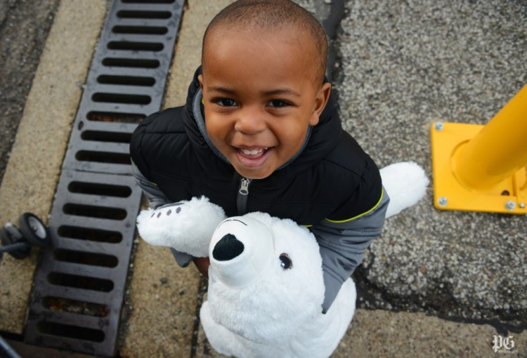 Isaias Baker, 1, of the Hill District is happy to get a stuffed polar bear at the Toys for Tots in the Strip District on Saturday, December 12, 2015. Toys for Tots holds an open house Dec.12 to distribute toys to parents and guardians of needy children at Guardian Storage Solutions. Lake Fong/Post-Gazette