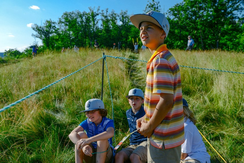 Jacob Kunc, foreground, 10, of Glenshaw, along with Logan Kozak, left, 10, of Gibsonia and Aidan Petroff, back center, 9, of Natrona Heights and Jack Rosensteel, 9, right, watch as group of golfers tee off from hole 4 during the second round. (Rebecca Droke/Post-Gazette)