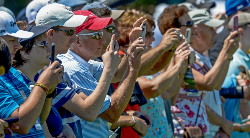 Spectators take cell phone photos along the second hole during practice rounds for the U.S. Open on Tuesday. (Matt Freed/Post-Gazette)