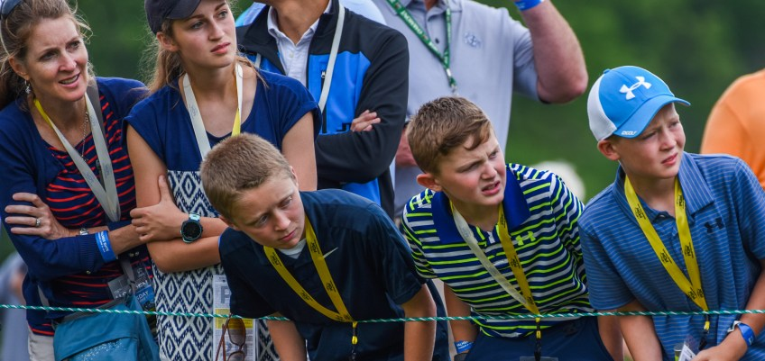 Young golf fans watch the flight path of balls teed off at the 18th hole during opening day. (Steve Mellon/Post-Gazette)
