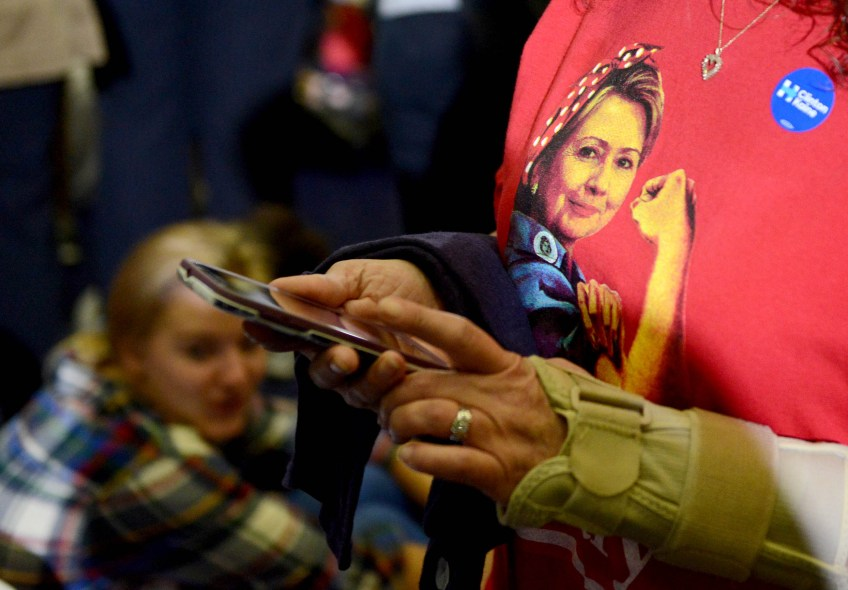 A woman wears a shirt depicting Hillary Clinton as Rosie the Riveter as people gather to watch Michelle Obama.