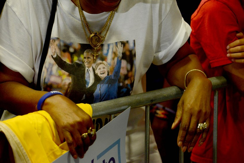 A woman wears a shirt with a photograph of President Barack Obama and Hillary Clinton.