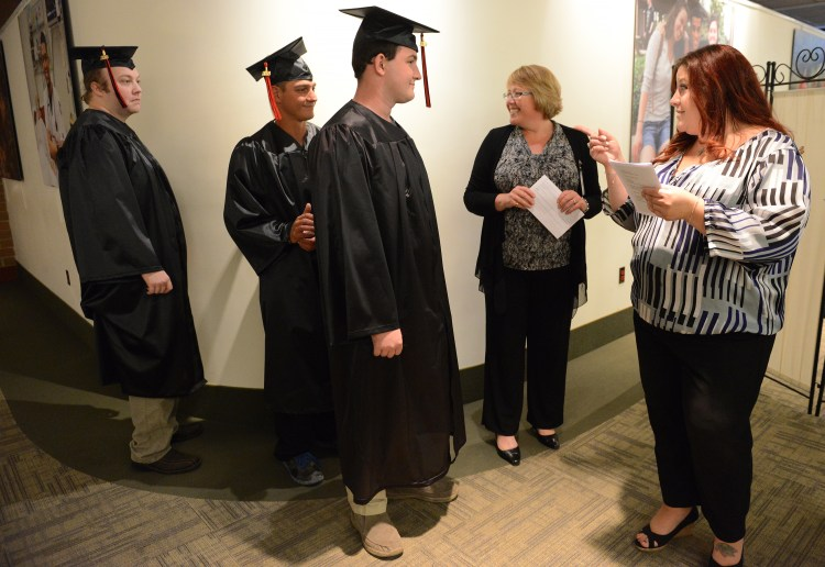 "Michelle Suriano, former director of finance at ITT Technical Institute, right, jokes with ITT students from left Zach Harshman, Lucas Borghi and Kalen Bailey, as she helps them line-up for commencement during a ceremony at Pittsburgh Technical Colleges in Oakdale Wednesday, October 12, 2016. Ms. Suriano said during her address to the students, ""You guys are the last class form ITT. For all of us at ITT this is the end of a journey and the start of a new one."""