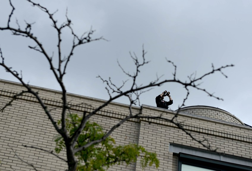 A spotter keeps watch from a roof at Carnegie Mellon University during The White House Frontiers Conference on Thursday, Oct. 13, 2016. (Photo by Michael Henninger/Post-Gazette)