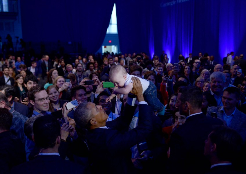 President Barack Obama picks up Rowan Wright, 10 and a half months, the son of Forest Wright, while greeting attendees at The White House Frontiers Conference at Carnegie Mellon University. (Photo by Michael Henninger/Post-Gazette)